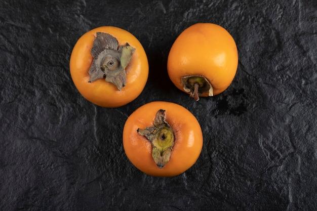Trois fruits kaki mûrs placés sur une surface noire