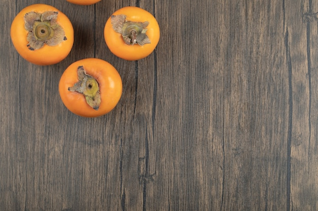 Trois fruits kakis mûrs placés sur une surface en bois