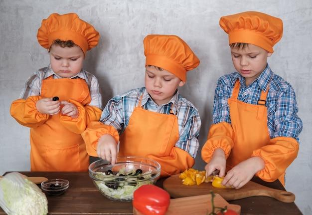 Trois garçons européens mignons en costumes orange cuisinent préparer une salade de légumes. préparer un dîner en famille