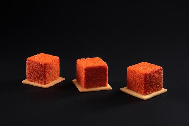 Trois gâteaux carrés orange avec une surface mate en ligne.