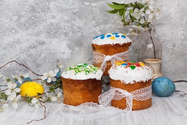 Trois gâteaux de pâques avec de la poudre colorée en forme de cœur et des œufs colorés