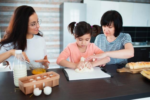 Trois générations de femmes cuisinent dans la cuisine. grand-mère, mère apprend à sa petite-fille à cuisiner. ils pétrissent la pâte ensemble.