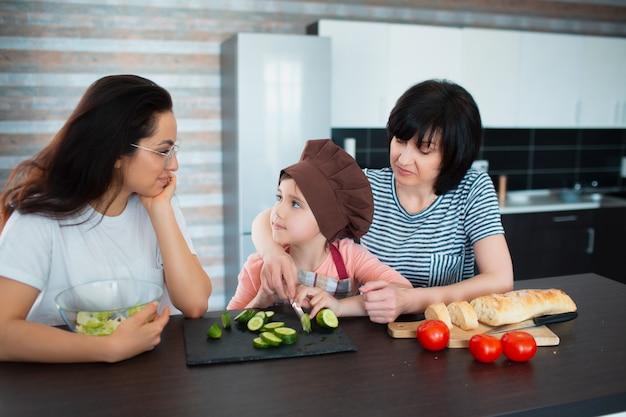 Trois générations de femmes cuisinent dans la cuisine. grand-mère, mère et petite-fille passent du temps ensemble à la maison.