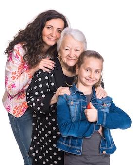 Trois générations de femmes sur un mur blanc