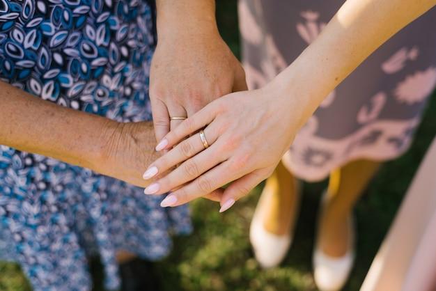 Trois générations. mains d'une fille, mère et grand-mère un à un
