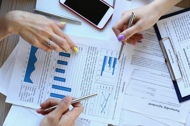 Trois gestionnaires discutant du tableau financier au bureau