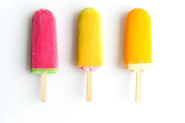 Trois glaces de couleurs différentes s'alignent sur un fond blanc. dessert rafraîchissant d'été.