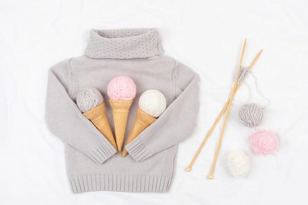 Trois glaces à partir de cônes de fil et de gaufres sur un pull en tricot gris, des aiguilles à tricoter en bois et une étoile sur fond blanc. tricot, passe-temps et concept fait main. vue de dessus mise à plat.