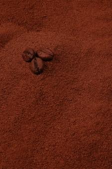 Trois grains de café sur un fond de café moulu