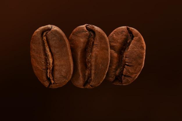 Trois grains de café torréfiés frais isolés sur un fond marron.
