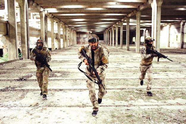 Trois guerriers avec équipement dévalent une grande pièce lumineuse.
