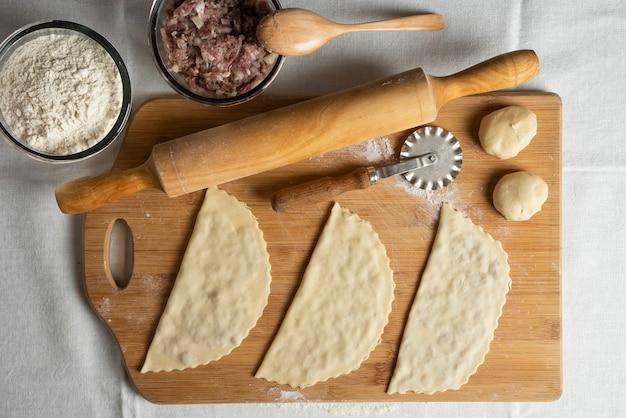 Trois gutabs de viande non cuits sur planche de bois. cuisine nationale azerbaïdjanaise.