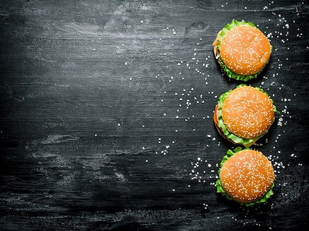 Trois hamburgers avec viande, fromage et légumes frais. sur un tableau noir. vue de dessus.