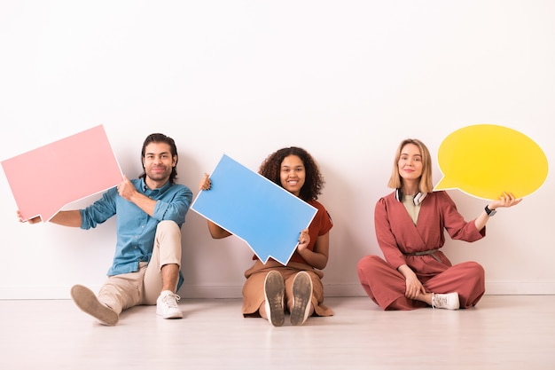 Trois heureux jeunes milléniaux interculturels en tenue décontractée montrant de grandes bulles de papier de couleur alors qu'il était assis le long du mur blanc