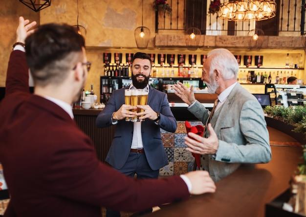 Trois hommes d'affaires célébrant le travail accompli avec succès au restaurant.