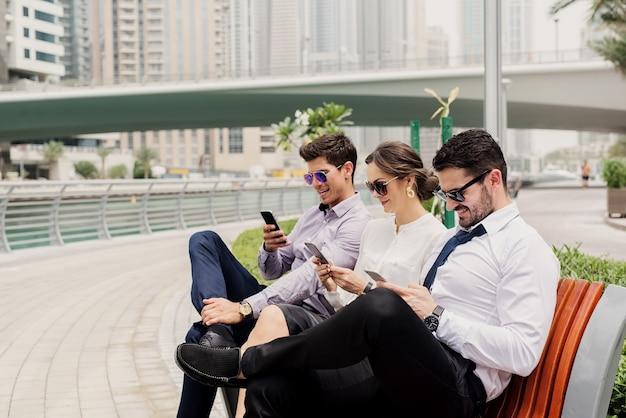 Trois hommes d'affaires en costume prenant une pause de travail acharné. s'asseoir dehors dans la marina de dubaï et s'amuser à surfer sur internet.