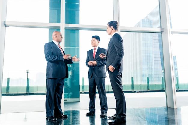 Trois hommes d'affaires debout dans le hall du bureau