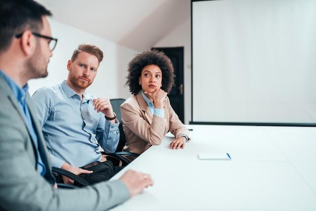 Trois hommes d'affaires du millénaire sérieux discutant à la table de la salle de réunion