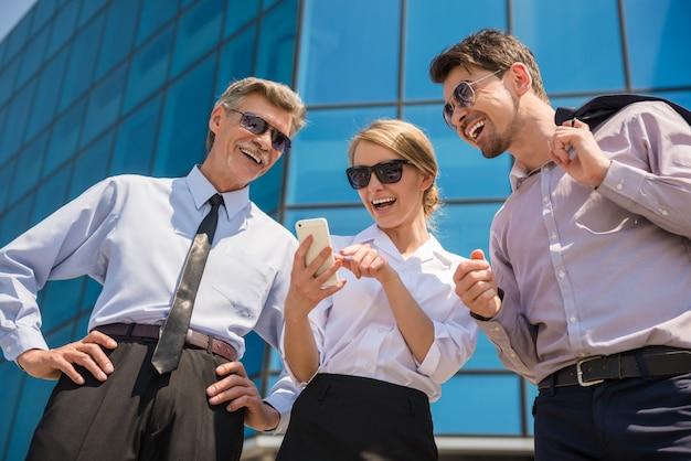 Trois hommes d'affaires prospères en costume regardant téléphone.