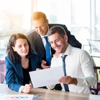 Trois hommes d'affaires regardant un rapport d'activité au bureau