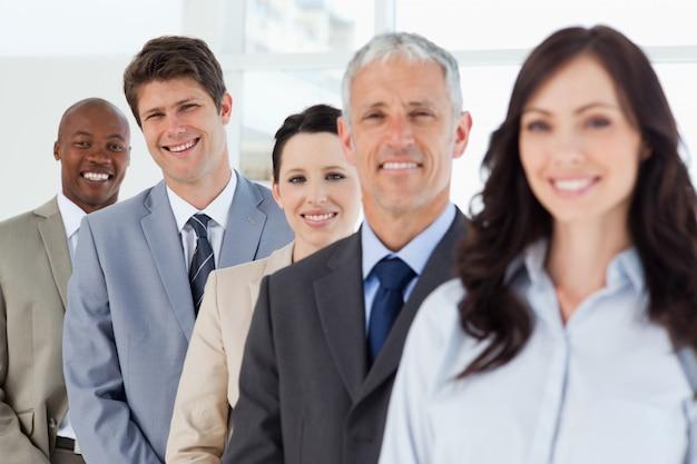 Trois hommes d'affaires souriants en arrière-plan à la suite de leurs dirigeants