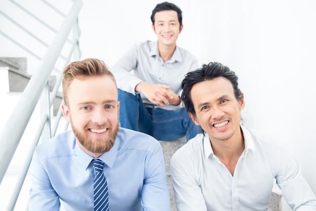 Trois hommes d'affaires souriants assis à l'escalier