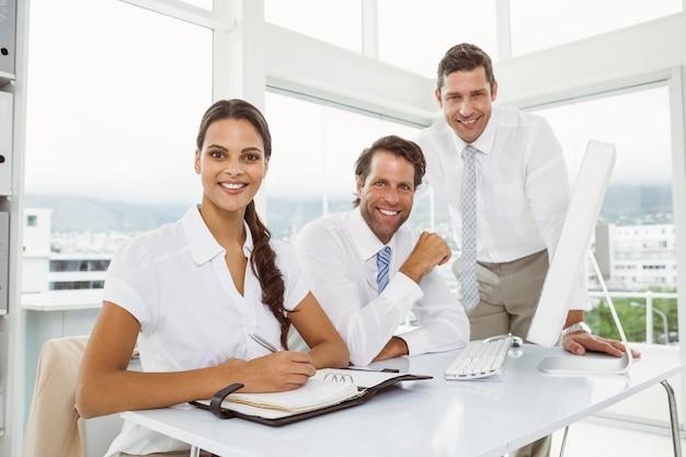 Trois hommes d'affaires souriants au bureau
