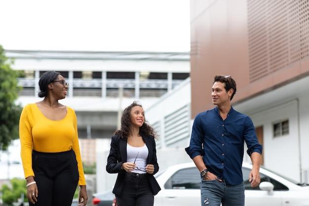 Trois hommes d'affaires souriants discutant d'une réunion en marchant dans la ville.