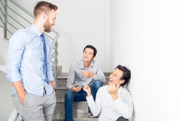 Trois hommes d'affaires souriants en train de discuter sur les escaliers