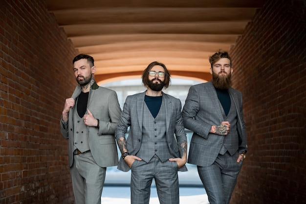 Trois hommes en costumes gris se tiennent dans un tunnel de briques