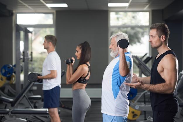 Trois hommes et une femme s'entraînant quotidiennement au gymnase.