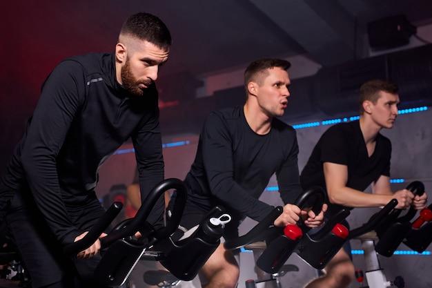 Trois hommes en forme s'exerçant et s'entraînant dans une salle de sport, vélo de machine à vélo, portant un survêtement. entraînement, santé, bien-être en forme