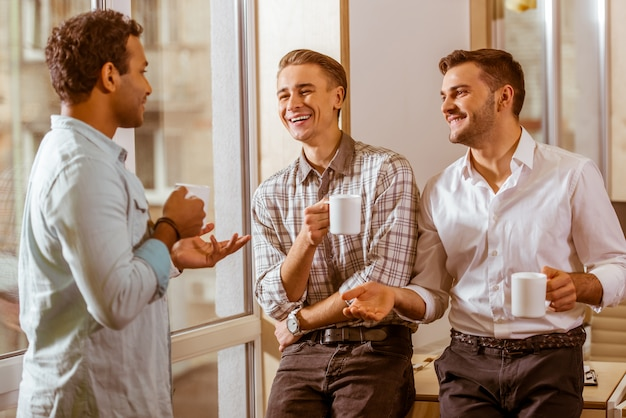 Trois hommes se tiennent dans le bureau et discutent de l'idée d'entreprise.