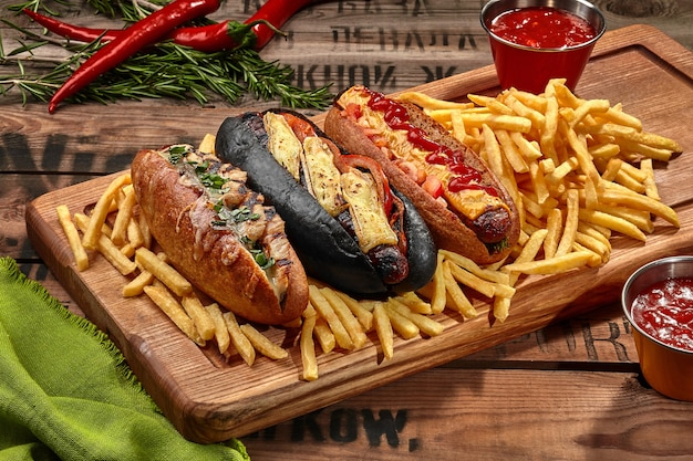 Trois hot-dogs sur planche de bois avec frites et sauce
