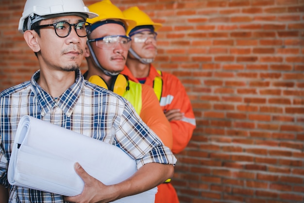 Trois ingénieurs ou architectes du bâtiment asiatiques avec l'idée de travailler en équipe de construction - les superviseurs et les suiveurs se tiennent dans la zone de construction