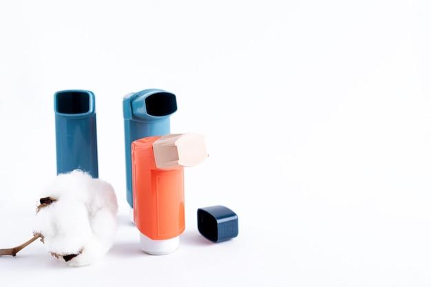 Trois inhalateurs d'asthme sur un fond blanc isolé. notion médicale.