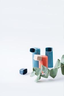 Trois inhalateurs pour l'asthme et une branche d'eucalyptus sur un isolé sur blanc. mise au point sélective.