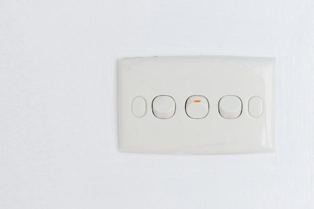 Trois interrupteur de lumière sur deux et un trunon sur le mur blanc