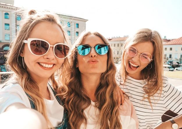 Trois, jeune, sourire, hipster, femmes, dans, vêtements été., filles, prendre, selfie, autoportrait, photos, sur, smartphone., modèles, poser, dans, les, street., femme, projection, positif, figure, émotions, dans, lunettes soleil