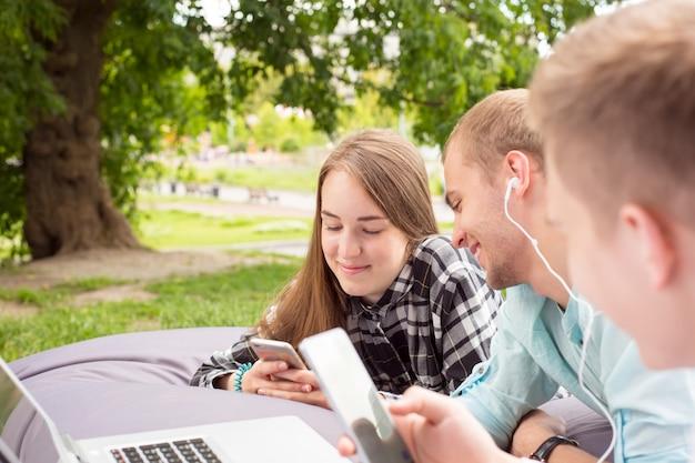 Trois jeunes amis couchés sur un grand coussin et se détendre en plein air avec leur téléphone.