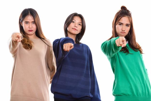 Trois jeunes amis de femme asiatique doigt pointé