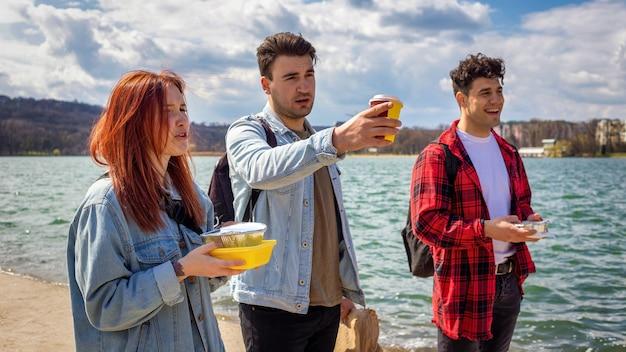 Trois jeunes amis marchant le long du lac, buvant et mangeant dans un parc