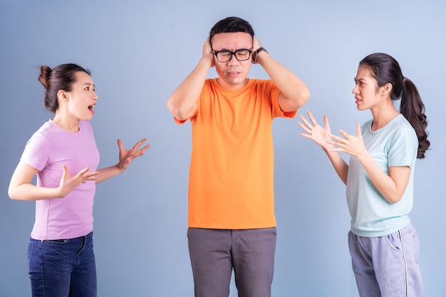 Trois jeunes asiatiques posant sur fond bleu