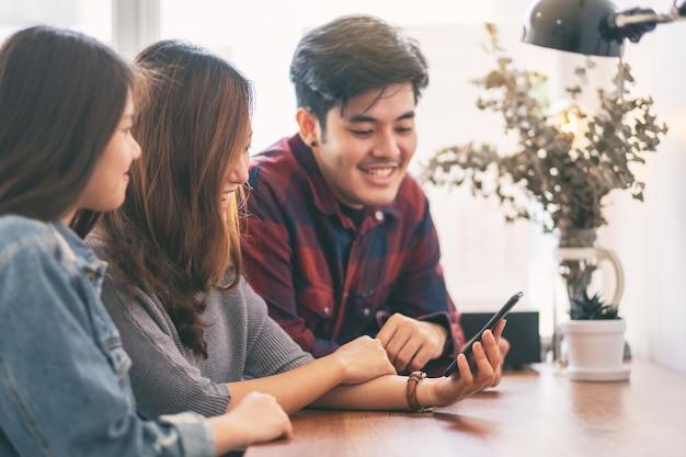 Trois jeunes asiatiques utilisant et regardant ensemble le même téléphone portable