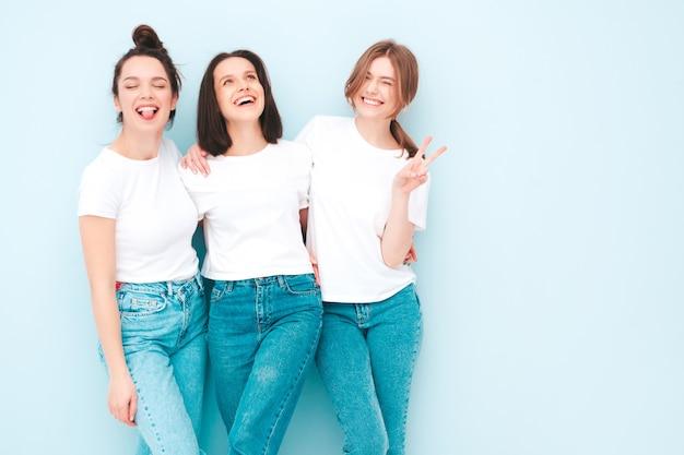 Trois jeunes belles femmes hipster souriantes dans des vêtements en jean et t-shirt blancs à la mode du même été