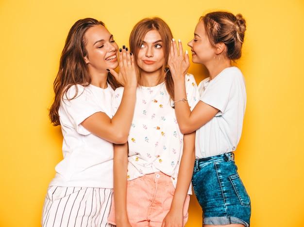 Trois jeunes belles filles hipster souriantes dans des vêtements d'été à la mode. femmes insouciantes sexy posant près du mur jaune. les mannequins positifs deviennent fous et s'amusent.