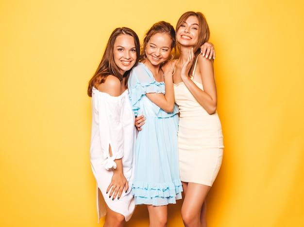 Trois jeunes belles filles hipster souriantes dans des vêtements d'été à la mode. femmes insouciantes sexy posant près du mur jaune. des modèles positifs qui deviennent fous et qui s'amusent