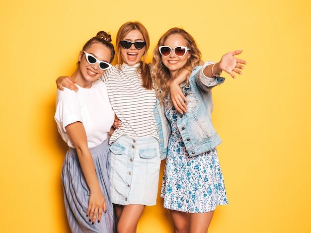 Trois jeunes belles filles hipster souriantes dans des vêtements d'été à la mode. femmes insouciantes sexy posant près du mur jaune. modèles positifs s'amusant avec des lunettes de soleil
