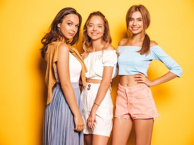 Trois jeunes belles filles hipster souriantes dans des vêtements d'été à la mode. femmes insouciantes sexy posant près du mur jaune. modèles positifs s'amusant