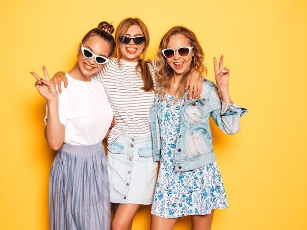 Trois jeunes belles filles hipster souriantes dans des vêtements d'été à la mode. femmes insouciantes sexy posant près du mur jaune. des modèles positifs s'amusent et montrent un signe de paix